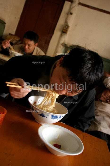 Young Chinese men eat noodles and dumplings in the Old Town, Shanghai, China. - Jess Hurd - 2003-10-26