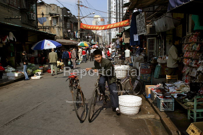 Young Chinese man with bicycles in the Old Town Ghost Market, Shanghai, China. - Jess Hurd - 2003-10-26