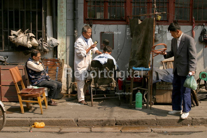 Man gets a haircut on the pavement in the Old Town, Shanghai, China. - Jess Hurd - 2003-10-20
