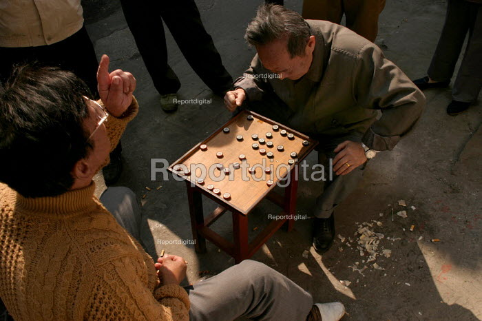 Chinese men play the strategic and deterministic board game GO in the Old Town, Shanghai, China. - Jess Hurd - 2003-10-26