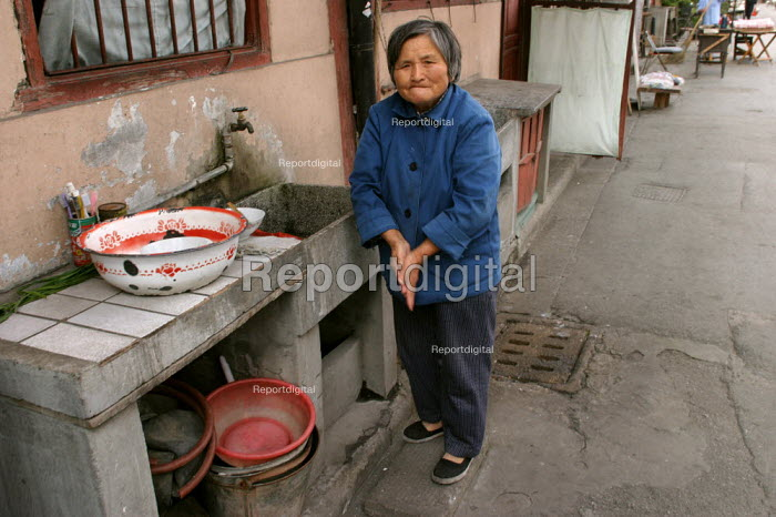 Old Chinese woman washes using a sink in the street. Old Town, Shanghai, China. - Jess Hurd - 2003-10-26