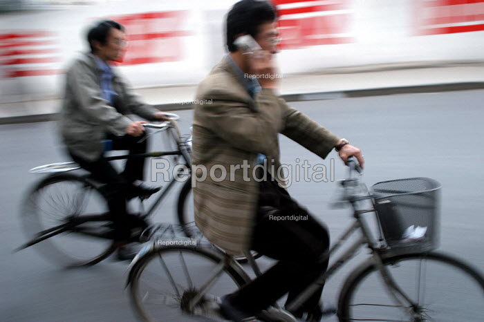 Man cycles to work on a bicycle talking on his mobile telephone. Shanghai, China. - Jess Hurd - 2003-10-20