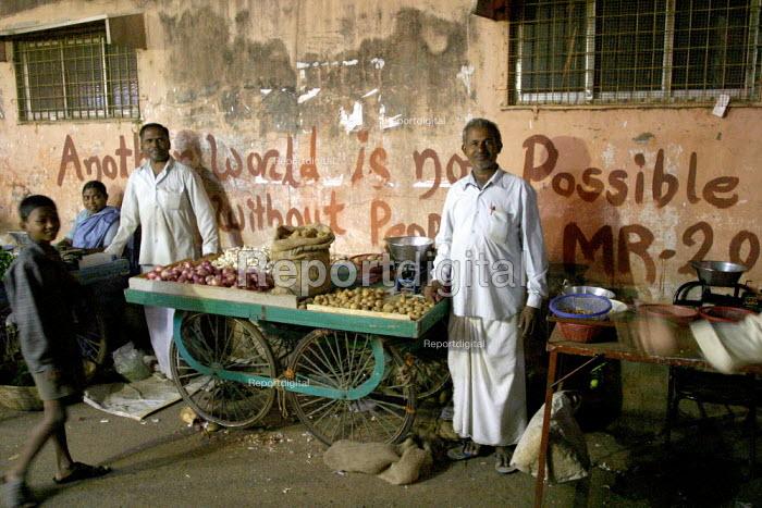 Anti Capitalist graffiti at night street market. World Social Forum, Mumbai, India. - Jess Hurd - 2004-01-23