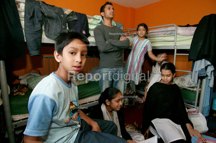 Children try to do their homework in a cramped bedroom. Bengali family, Sanur Ali with wife Salima Begum and their five children living with two other relatives in a damp and crowded two bedroom council flat in Tower Hamlets. They are trying to get re housed by the council but are not seen as a priority case. East London. - Jess Hurd - 2004-10-02