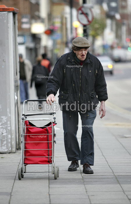 Man with a shopping basket walks down Bethnal Green Road, London. - Jess Hurd - 2004-11-27