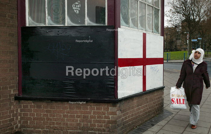 A young asian woman walks past St Georges Flag with Racists scrawled on it outside an East London Pub. - Jess Hurd - 2005-01-01