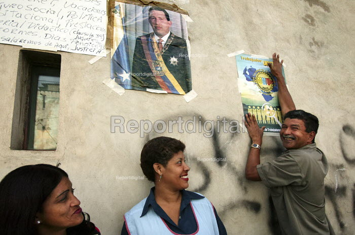 Workers at Selfex Textile Factory put up images of Hugo Chavez. The workers are occupying the building demanding co-management .The action by members of the Unete trade union is supported by the government of President Hugo Chavez. Caracas, Bolivarian Republic of Venezuela. - Jess Hurd - 2006-01-19