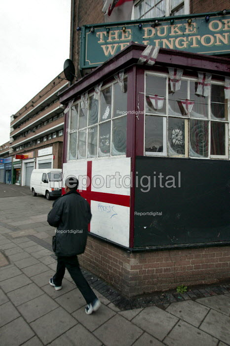 A young asian man walks past St Georges Flag with Racists scrawled on it outside an East London Pub. - Jess Hurd - 2005-01-01