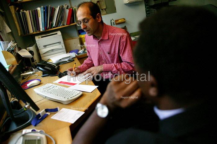 Doctor Kambiz Boomla advises a patient at Chrisp Street Health Centre. Tower Hamlets. - Jess Hurd - 2004-09-24