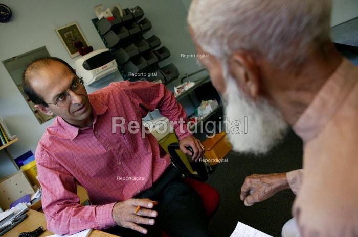 Doctor Kambiz Boomla advises a patient at Chrisp Street Health Centre. Tower Hamlets, London - Jess Hurd - 2004-09-24