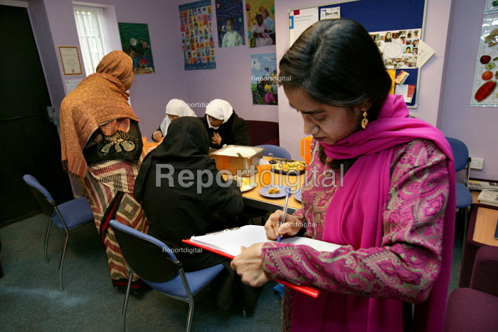Community project worker takes the register of attendance at the Healthy Eating Lunch Club at the Ocean Womens Centre, Ocean Estate, Tower Hamlets, East London. - Jess Hurd - 2005-01-19