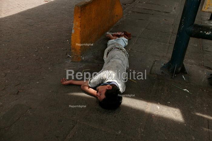 Homeless man sleeps rough in a bus shelter, Porto Alegre Brazil. - Jess Hurd - 2005-01-30