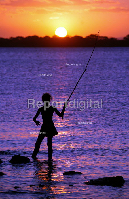 Young Brazilian girl fishes as the sun sets on the World Social Forum, Porto Alegre Brazil. - Jess Hurd - 2005-01-30