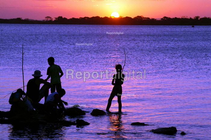 Brazilian family fishing as the sun sets on the World Social Forum, Porto Alegre Brazil. - Jess Hurd - 2005-01-30
