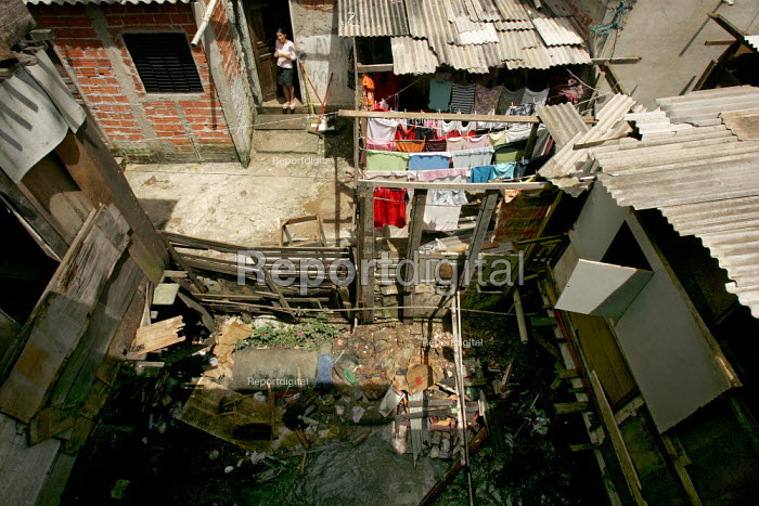 Woman looks out on an open sewer running though her back yard. Heliopolis Favela on the outskirts of Sao Paulo where families live in slum housing, Brazil. - Jess Hurd - 2005-02-08