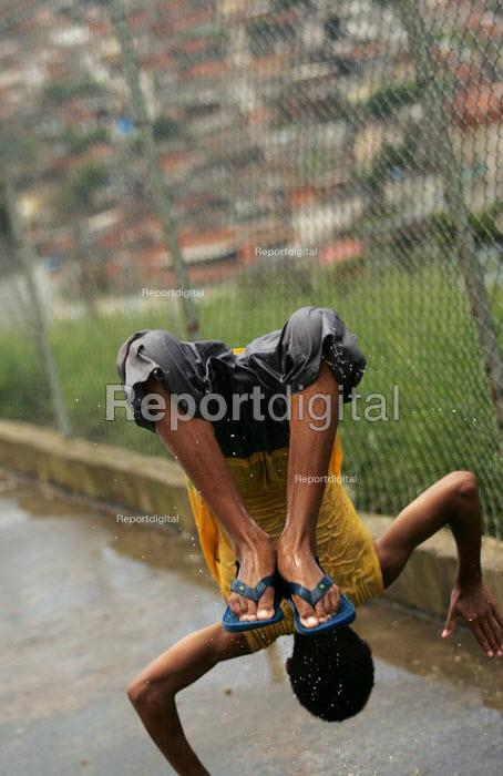 Teenager playing in the rain, Magdalena Favela, Sao Paulo where families live in slum housing, Brazil. - Jess Hurd - 2005-02-03