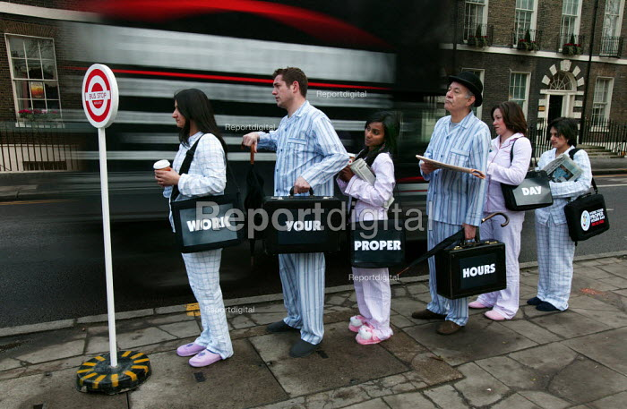Commuters queue at a mock bus stop on Bedford Square London W1, dressed in pyjamas and slippers to promote the TUC Work Your Proper Hours Day. London. - Jess Hurd - 2005-02-23
