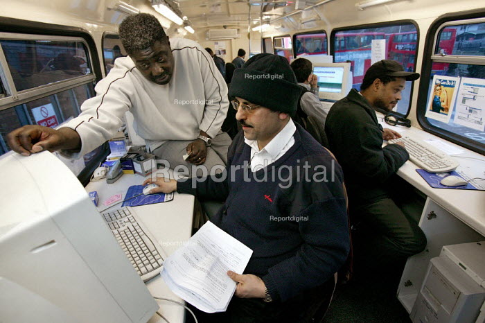 Computer tutor with a Metrolink bus driver on the Computer Training Bus at Willesden Bus Garage. London. - Jess Hurd - 2005-03-08