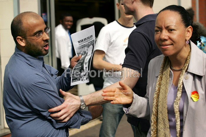 A member of the public is dragged away by a Labour Party minder as he tackles Oona King MP on the legitimacy of the war in Iraq. Labour Party General Election campaign stall in Bethnal Green and Bow. London. - Jess Hurd - 2005-04-02