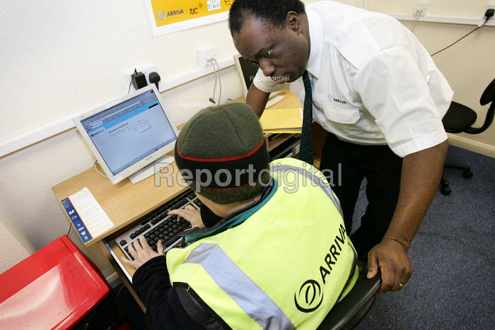 Learning Rep and TGWU Trade union representative helps a bus driver with computer skills. Learning Facilities room at Tottenham Arriva Bus Garage. London. - Jess Hurd - 2005-03-09