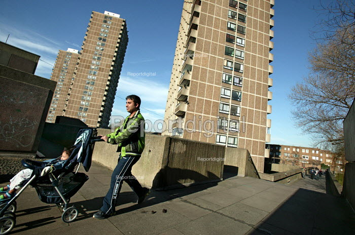 Father with child in a push chair on the 1970's Crossways Estate which is due for demolition. Tower Hamlets, East London - Jess Hurd - 2005-03-18