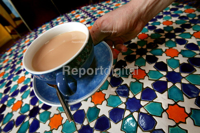Waiter serves a cup of tea served at Cafe Eat 2, Bethnal Green. London. - Jess Hurd - 2005-03-22