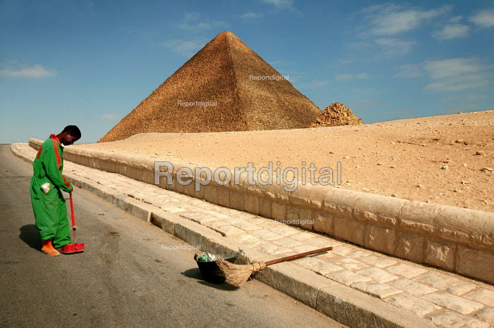 Street cleaner sweeps at the base of the Pyramid of Khufu, Cheops c.2585-2560 B.C.E., the largest of the three principal pyramids on the Giza Plateau. Cairo, Egypt. - Jess Hurd - 2005-03-24