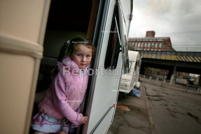 Young girl looks out of her caravan onto a bleak traveller site with no facilities. The site is overlooked by Bow Quarter - a luxury gated development in Tower Hamlets, East London. - Jess Hurd - 2005-04-06
