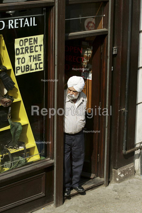 Worker outside shop and leather goods suppliers nr Brick Lane, Tower Hamlets, East london. - Jess Hurd - 2005-04-02