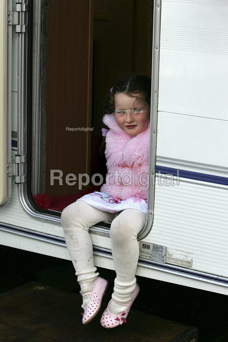 Young girl looks out of her caravan on a traveller site next to Bow Quarter - a luxury gated development in Tower Hamlets, East London. - Jess Hurd - 2005-04-06