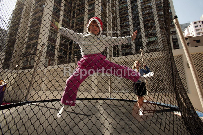 English children play on a trampoline on the terrace of their apartment. Most of Hong Kongs population live in cramped accommodation. Hong Kong. - Jess Hurd - 2005-12-18