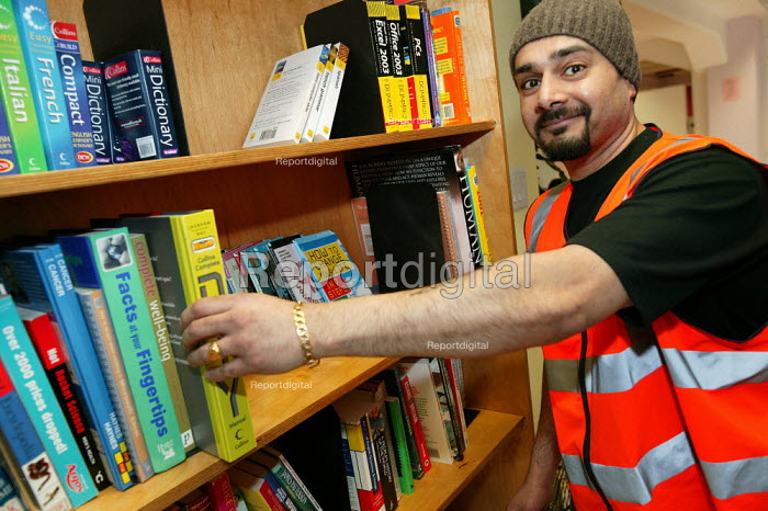 World Book Day at Mount Pleasant Sorting Office. Royal mail worker with a new book borrowing shelf at Mount Pleasant Sorting Office in North London. - Jess Hurd - 2006-03-02