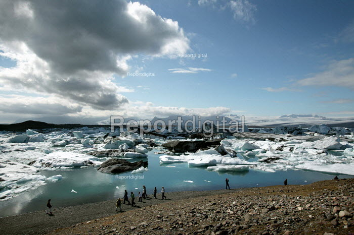 Tourists enjoy the view at the rapidly expanding Jokulsar Lagoon with icebergs created from the retreating Breidamerkurjokull glacier which is an outlet glacier of Vatnajokull, the largest ice cap in Europe. Iceland. - Jess Hurd - 2006-07-22