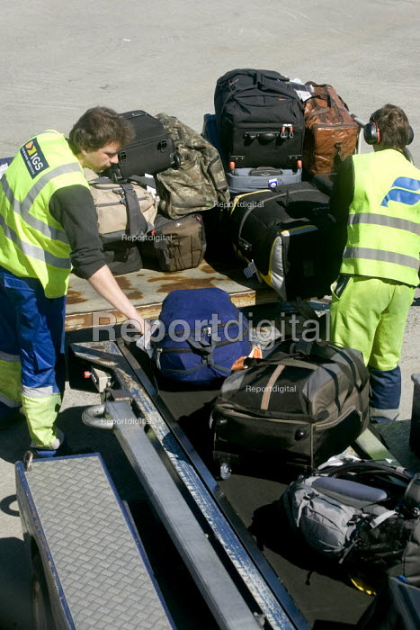 IGS Ground Services baggage handlers unloading luggage from a plane at Rekyivik Airport, Iceland. - Jess Hurd - 2006-07-20