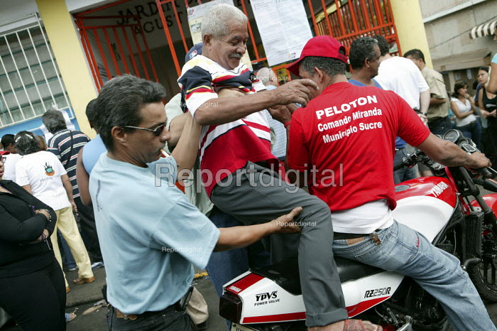 Elderly disabled man is given a lift to the polling station on a motorbike taxi in Petare the largest Barrio in Latin America. Presidential election campaign, Caracas, Bolivarian Republic of Venezuela. - Jess Hurd - 2006-12-03
