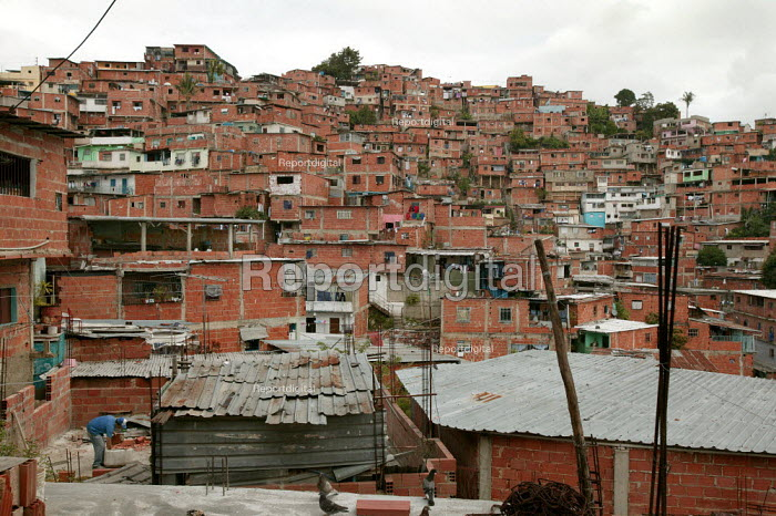 Man builds his own house with bricks provided by a government scheme. Barrio Petare, Caracas. Bolivarian Republic of Venezuela. - Jess Hurd - 2006-01-27
