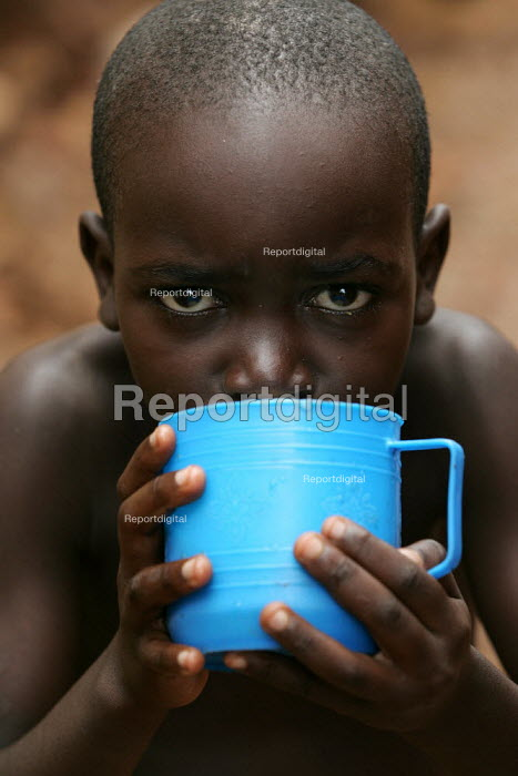 Child drinks some water in Kibera - the largest slum in Africa. Nairobi, Kenya. - Jess Hurd - 2005-06-25