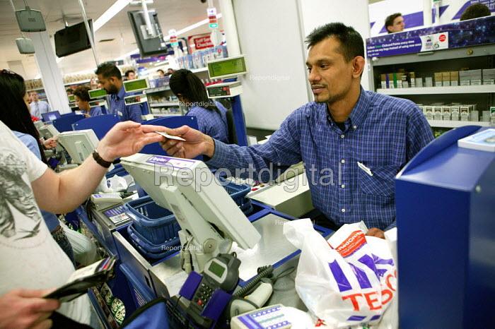 Staff working at the checkout. Tesco Metro, Bishopsgate, London. - Jess Hurd - 2007-04-17