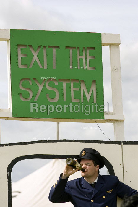 Protestor dressed as a pilot gets drunk at the entrance to the Camp for Climate Action at Heathrow, the world's busiest airport and a big source of CO2 emissions. London. - Jess Hurd - 2007-08-17
