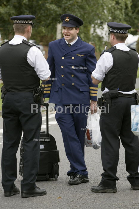 Protestor dressed as a pilot is stopped at the camp cordon by police. Camp for Climate Action at Heathrow, the worlds busiest airport and a big source of CO2 emissions. London. - Jess Hurd - 2007-08-15