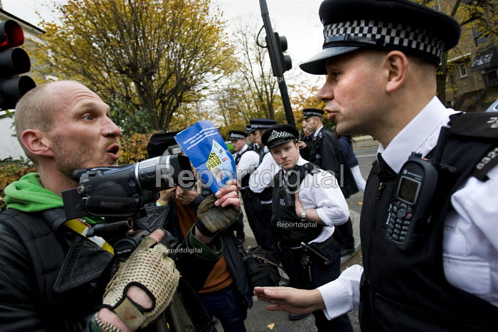 Video Journalist holds up a copy of the police media guidelines whien restricted from leaving a cordon. Bash The rich, Class War demonstration, Notting hill. London. - Jess Hurd - 2007-11-03