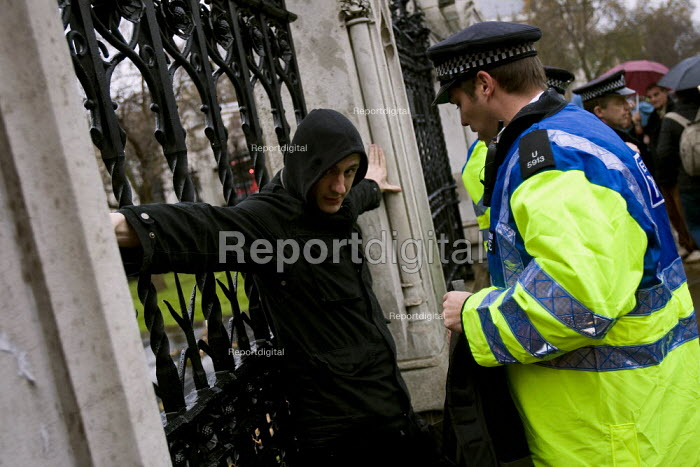Police Stop and Search a protester outside the gates of Parliament before he joins the International Climate Protest, London. - Jess Hurd - 2007-12-08