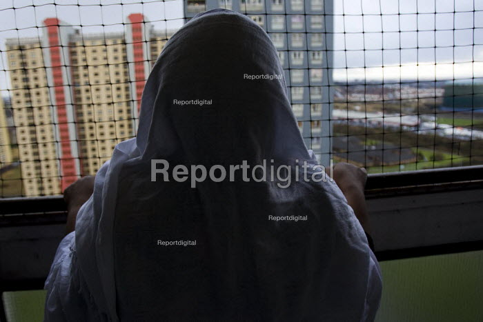 Asylum seeker looks out the window of her Red Road Flats, Glasgow, Scotland. - Jess Hurd - 2007-12-29