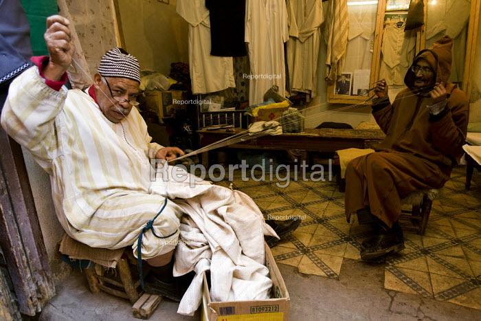 Craftsman makes the traditional jelaba, Marrakech, Morocco. - Jess Hurd - 2008-01-12