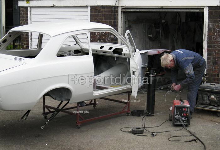 Man works on rebuilding a car on an estate in East london. A Mk1 Ford Escort 2 door. - Jess Hurd - 2008-02-03