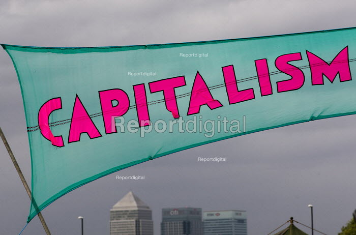 Canary Wharf and Capitalism is crisis banner. Climate Camp protestors establish on Blackheath. South East London. - Jess Hurd - 2009-08-26