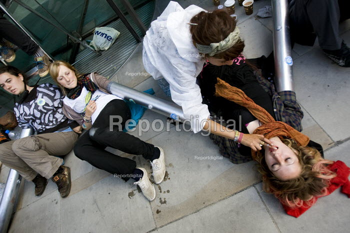 Protester applies lip gloss to locked down demonstratior. Climate Camp action outside RBS, Liverpool St, City of London. - Jess Hurd - 2009-09-01