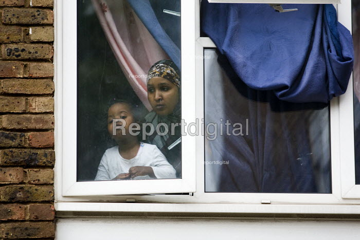 Mother and child look out of their window at English Defence League supporters. Anti-fascist demonstrators and local muslim youths gathered to counter a threatened march by right wing groups outside Harrow Central Mosque. London. - Jess Hurd - 2009-09-11