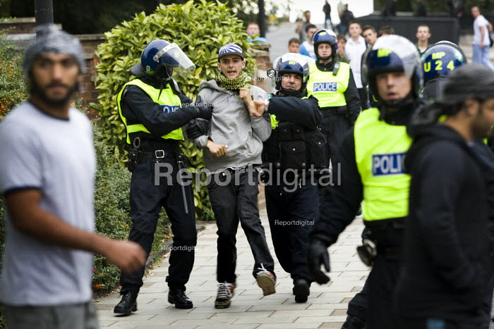 Police arrest a young asian man. Anti-fascist demonstrators and local muslim youths gathered to counter a threatened march by right wing groups outside Harrow Central Mosque. London. - Jess Hurd - 2009-09-11