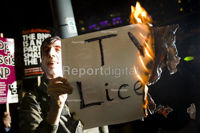 Burning the TV Licence in protest. Unite Against Fascism demonstration opposing the invitation of BNP leader Nick Griffin on Question Time. BBC Television Centre, White City. - Jess Hurd - 2009-10-22